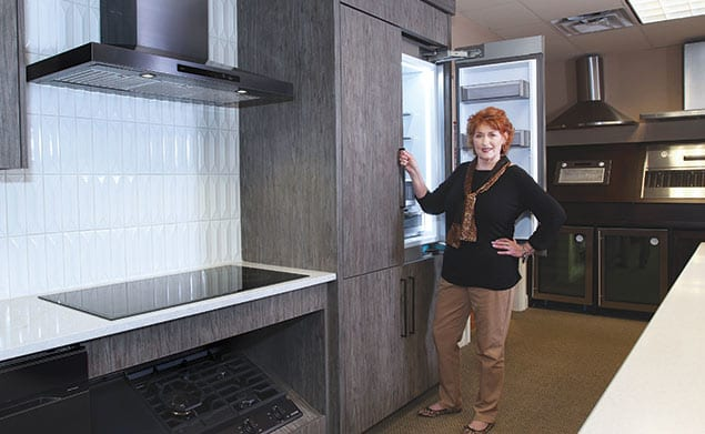 Linda Hosea stands in front of a refrigerator at Builder Specialties