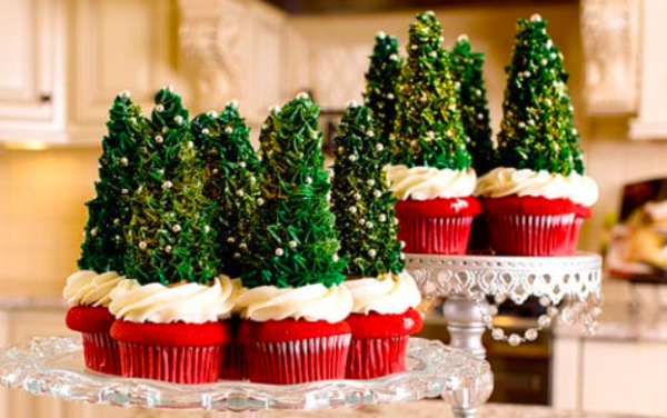 Icing piped Christmas Trees on top of red cupcakes