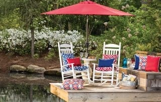 Outdoor living area decorated with red, white and blue cushions and umbrella