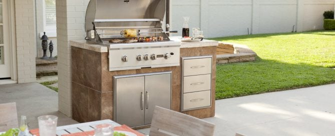 Outdoor kitchen in backyard featuring a Coyote Grill