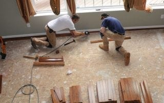 Men laying new hardwood flooring