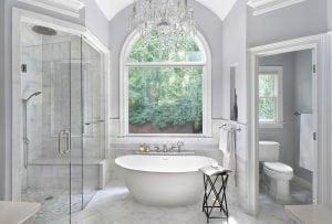 Large open bathroom with large stand alone white tub in front of feature window.
