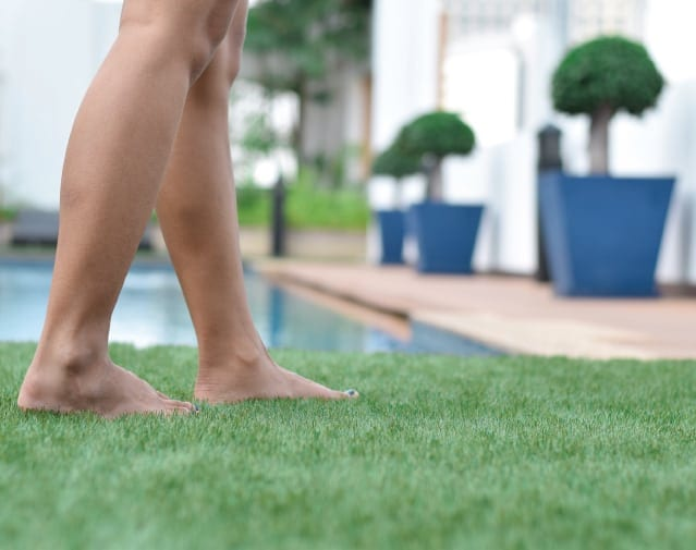Lady near a pool walking on TifTuff Bermuda grass - NG Turf