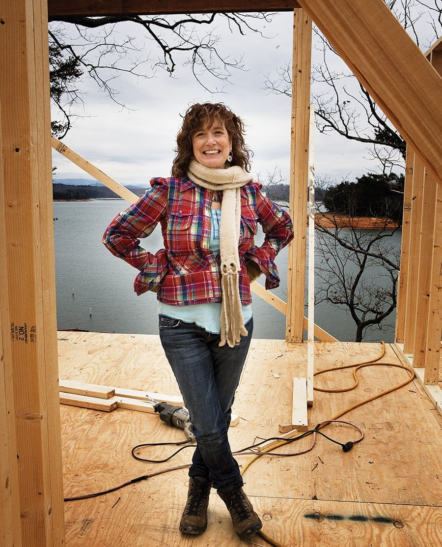 Judy Mozen of Handcrafted Home standing infront of a lake