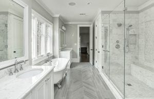 Narrow bathroom with marble one walls and floor. Standing bath tub in front of window.