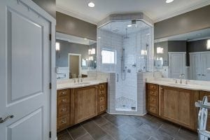 Traditional bathroom with two wood vanities flanking a feature shower.