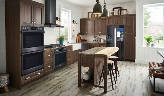 Beautiful kitchen with black Samsung appliances, brown built-in cabinetry and distressed hardwood flooring