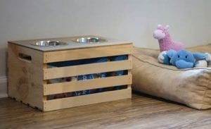 Crate Dog Feeder with storage for dog food and a dog bed with stuffed animals