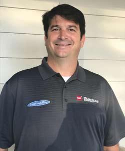 Smiling man wearing a black polo shirt