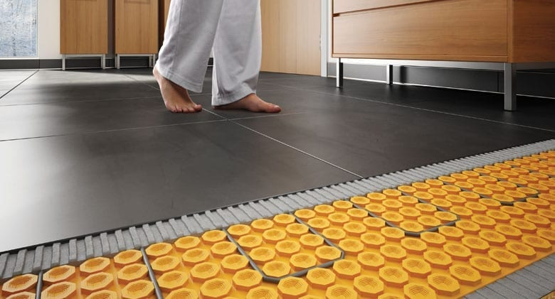Woman walking on tile flooring with Schluter DITRA HEAT floor warming system