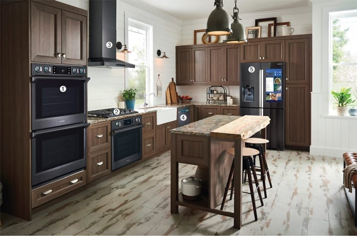 "Beautiful kitchen with brown cabinets, double built-in Wall Oven, 36"" Cooktop and vent hood and touch screen refrigerator"