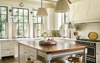 Farmhouse style kitchen with wood island and three bar stools