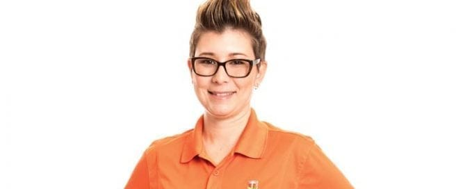 Lindsey Barnhill wearing an orange top with company logo