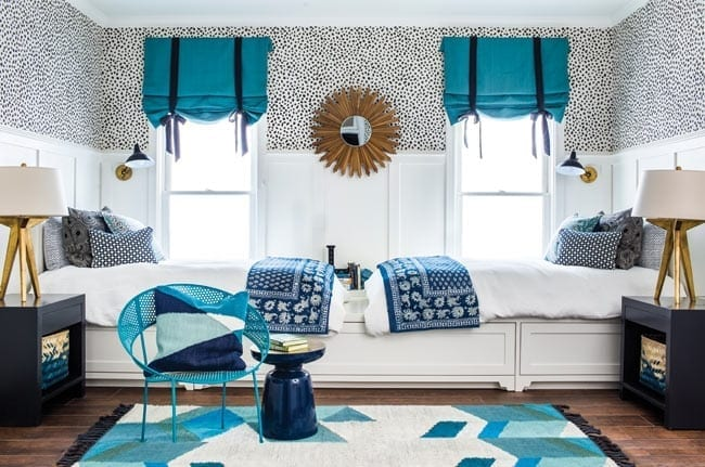 Blue and white kid's bedroom with two connected beds and a trundle bed