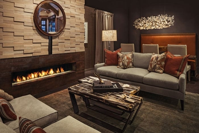 Living room with warm brown colors and lit spark gas fireplace