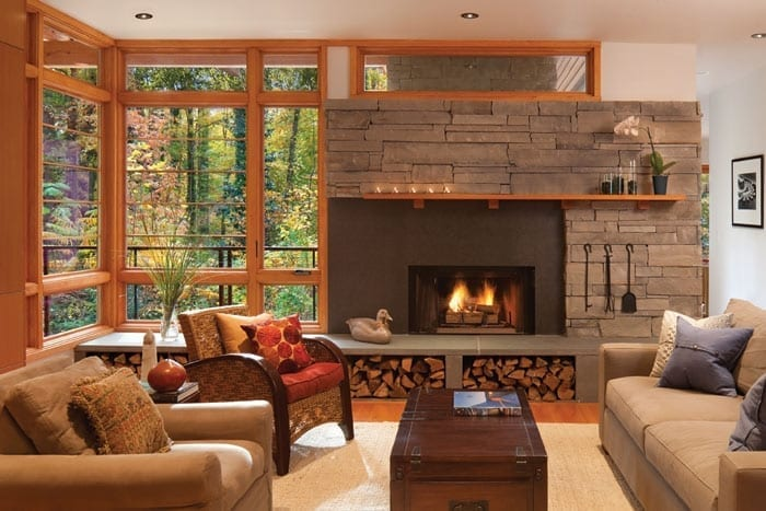 Living room with stacked stone fireplace and floor to ceiling windows