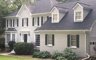 Two-story brick house painted white with black roof