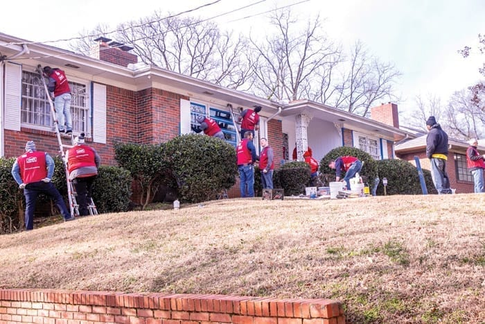 Volunteers from Lowe's work on the exterior of a home