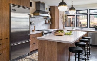 Gorgeous masculine kitchen design with geometric pendants and custom range hood
