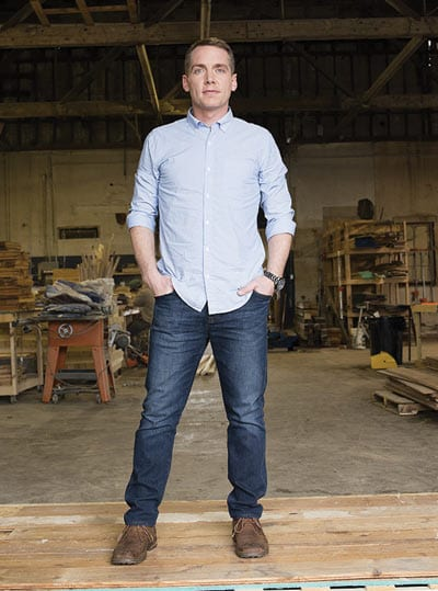 Clint Harp stands in a works shop wearing a blue long sleeved shirt and blue jeans