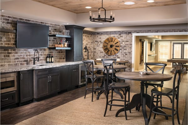 Brick basement with black cabinets and shelves, bar and game table