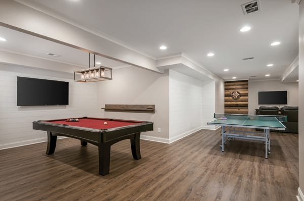 Basement entertainment room with pool and ping pong tables and large screen TVs