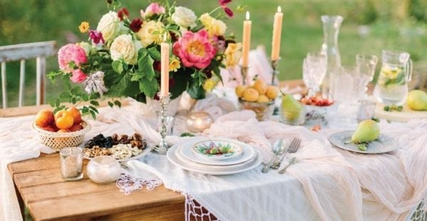Picnic table with flower, candles and food