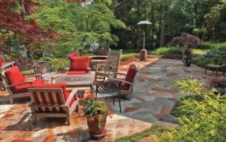 Beautiful backyard with brown and gray pavers, garden and patio chairs with red cushions