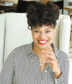 Beautiful, African American lady smiling in black and white striped blouse