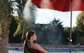 Woman sitting by pool under an umbrella with a misting system