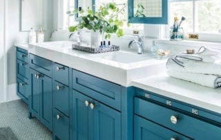 Bathroom with blue cabinets with decorative pulls and white countertop