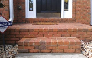 Brick steps leading up to a white door