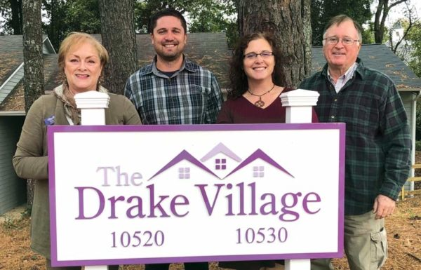 Two men and two women holding a sign that says The Drake Village
