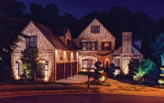 Night shot of a big brick house lit up with exterior lights