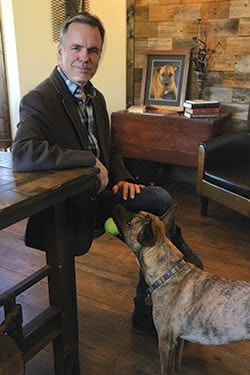 Male sitting with a dog standing beside him