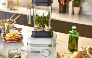 countertop with olive oil, pesto, blender