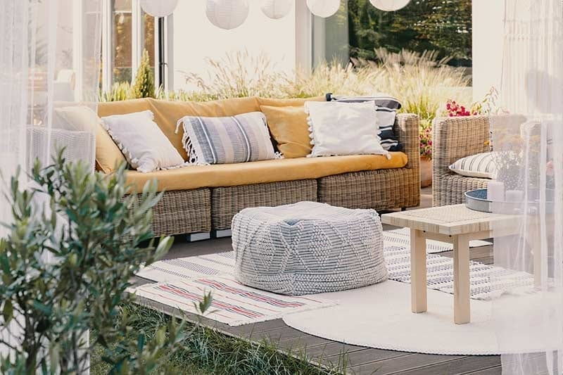 Relaxing outdoor space with outdoor furniture, rugs and pouf