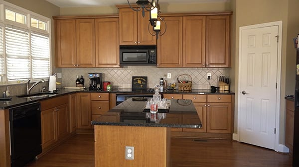 Dated kitchen with black countertop and brown wood cabinets