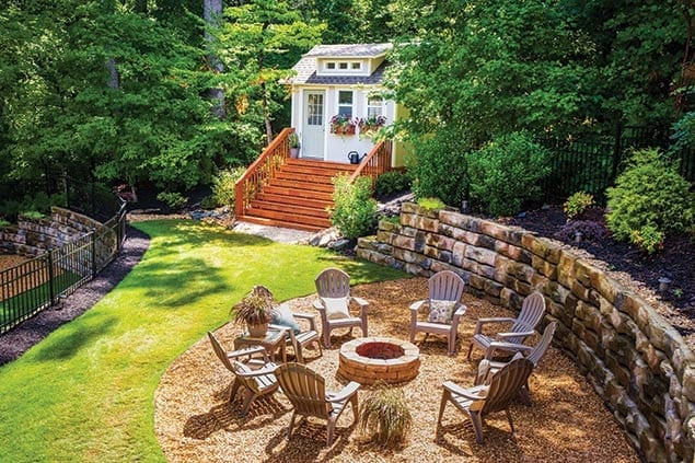 She shed surrounded by beautifully landscaped yard and firepit