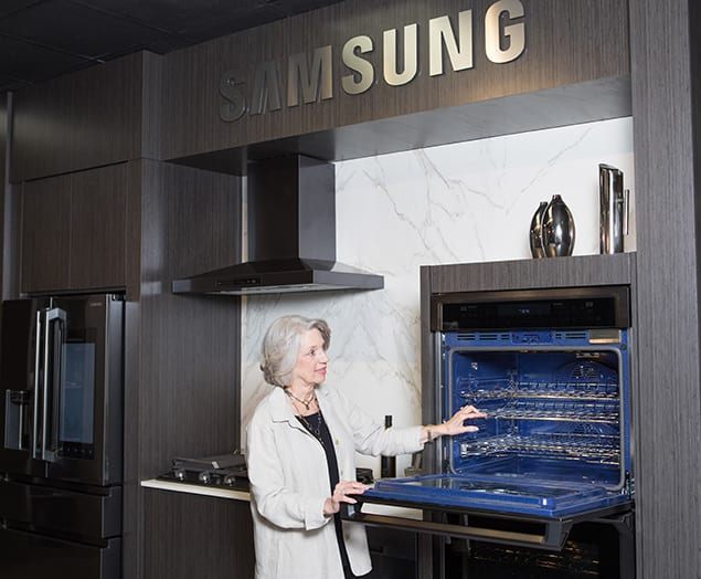 Howard Payne Company employee looks inside the chef collection Microwave oven
