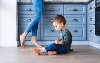 toddler sits on laminate flooring